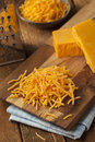 Organic shredded sharp cheddar cheese on a cutting board Royalty Free Stock Image