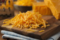 Organic shredded sharp cheddar cheese on a cutting board Royalty Free Stock Photography