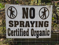 Organic sign posted on fence for no spraying near farm Royalty Free Stock Photos