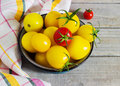 Organic yellow red cherry tomatoes with water drops in blue bowl Royalty Free Stock Photo