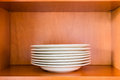 Organized minimalistic kitchen cabinet with a stack of white por Royalty Free Stock Photo