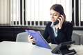 Organized responsible office worker business woman giving instructions via phone call.Looking confused checking notes and paperwor Royalty Free Stock Photo