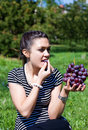 Oriental girl with grape Royalty Free Stock Photos