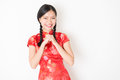 Oriental girl in red qipao greeting portrait of young asian traditional dress smiling and celebrating chinese lunar new year or Stock Photo