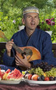 Oriental man playing mandolin dressed during breakfast at chaikhana uzbekistan summerhouse Royalty Free Stock Image