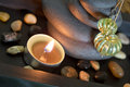 Oriental spa arrangement with candle and stones in black bamboo lamp Royalty Free Stock Photo