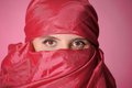 Oriental woman eyes a veiled on a red background Stock Photography