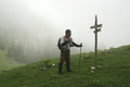 Orientation man reading a mountain sign orientating wearing trekking clothes and backpack holding poles in foggy weather Stock Images