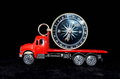 Orientation transportation concept compass on a red toy truck over black background Royalty Free Stock Photos