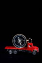 Orientation transportation concept compass on a red toy truck over black background Stock Photography