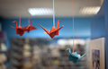 Origami birds hanging on ropes
