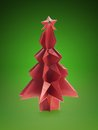 Origami christmas tree made from red paper shot over green background Stock Photos