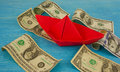 Origami paper boat at sea of money american moneys of hundred dollar on background Stock Images