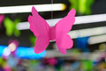 stock image of  Origami pink butterfly against the backdrop of neon bokeh