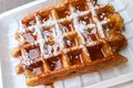 Original belgian waffle with caramel syrup and powdered sugar Royalty Free Stock Photography