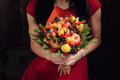 Original bouquet of vegetables and fruits the unusual edible in the girl hands on dark wooden background Royalty Free Stock Image