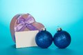 Original gift box heart christmas spheres and blank card on a blue background Royalty Free Stock Photo