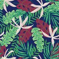 Original seamless pattern with bright tropical plants and leaves on a dark blue background. Vector design. Jungle print. Printing