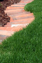 Ornamental garden bed and lawn grass path with made from baked clay tiles Stock Photography