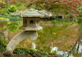 Ornamental stone lantern by a pond in a japanese garden in fall Stock Image
