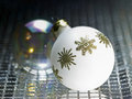Ornamented white christmas bauble in decorative metallic back Royalty Free Stock Photography