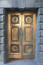Ornate bronze doors a pair of heavy guard the entrance to this grey stone building Royalty Free Stock Photography