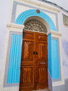 Ornate carved wooden door surrounded by blue stinework in the me Royalty Free Stock Photo