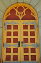 Ornate church door old red and yellow in wooden wall Royalty Free Stock Images