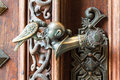 Ornate door handle an doorhandle of a castle where an asian man s head is pecked by a bird Royalty Free Stock Image