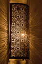 Ornate metal lamp glowing on marble wall Royalty Free Stock Image