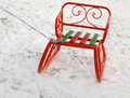 Ornate orange toboggan or sled in snow standing fresh white winter with a rope attached so that a young child can pull it up the Royalty Free Stock Photos