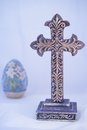 Ornate purple cross with easter lily egg gold filigree and has in background to offer seasonal decor Stock Image