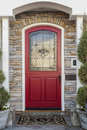 Ornate red front door of a home to family framed by stone detail and two white columns the has an pattern also seen is doormat and Royalty Free Stock Photo