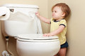 Ornery baby pulling toilet paper off the roll Royalty Free Stock Photography
