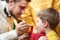Orthodox ceremony of the eucharist euharist priest makes child communion with bowl in church Royalty Free Stock Images