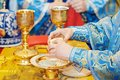 Orthodox christian euharist sacrament ceremony hands of priest refracting bread during liturgy Royalty Free Stock Photos