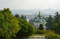 Orthodox church in the autumn park are photographed near wide river background there are residential districts of city Stock Photography
