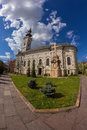 Orthodox church fisheye shot of an exterior with blue sky and few clouds in the background and grass lawn in the foreground Royalty Free Stock Image