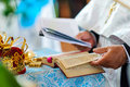 Orthodox priest during wedding ceremony photo presents holy bible crown and fragment of hand of crown is symbollic in church Stock Photography