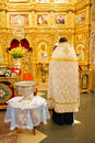 Orthodoxal priest in church preparing for christening ceremony Stock Images