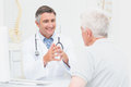 Orthopedic doctor discussing with senior patient male in clinic Royalty Free Stock Image