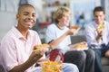 Os adolescentes que apreciam o fast food almoçam junto Foto de Stock Royalty Free