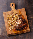 Osso buco veal shank with stewed cabbage tomatoes and on wooden cutting board on wooden background Royalty Free Stock Photos