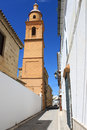 Osuna street with church tower andalusia spain narrow quiet cobblestone bell in Royalty Free Stock Photo