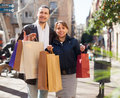 Ouple in jackets with purchases at street Stock Images