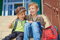 Our first day in school two happy kids brothers with book and backpack on stairs front of Stock Photo