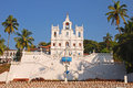 Our lady of the immaculate conception church front facade with stairs and coconut trees in old goa Royalty Free Stock Photo