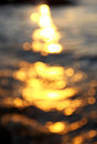 Out of focus bokeh background sea water with sun reflections Stock Photos