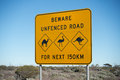 Outback road sign black on yellow safety warning on eyre highway in australia with camel emu and kangaroo against a blue sky Stock Photo