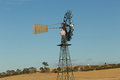Outback windmill repair a photograph of a farmer climbing a to it the photograph was taken on a hot summer morning on a sunny day Stock Photography